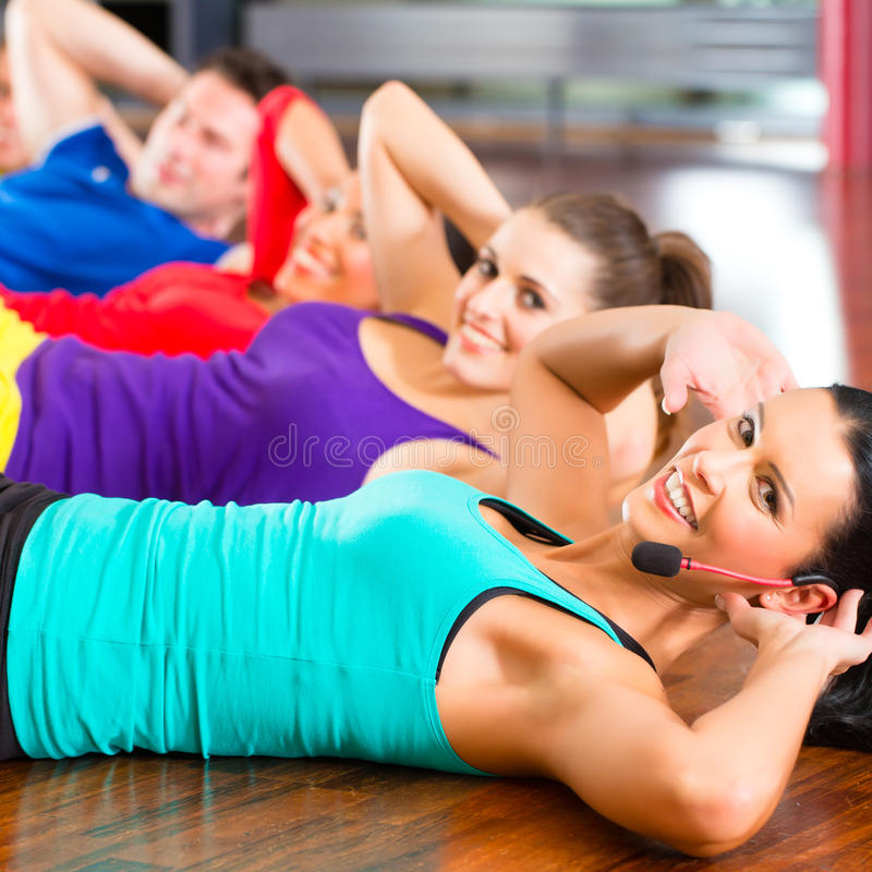 Fitness group in gym doing crunches for sport royalty free stock photography