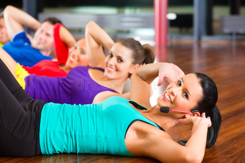 Fitness group in gym doing crunches for sport stock image