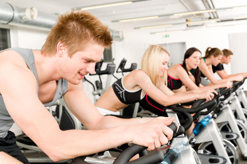 Fitness group of people on gym bike stock photography