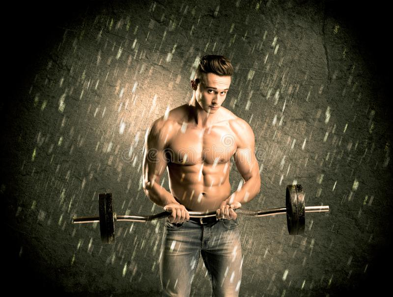 Fitness guy with weight showing muscles royalty free stock photography