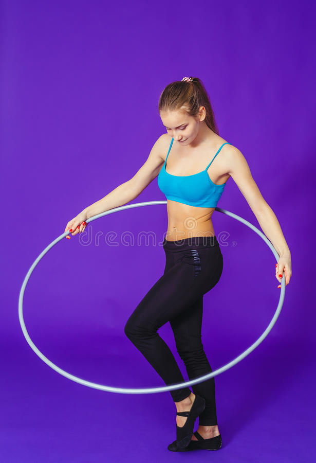 Fitness and gym concept - young sporty woman with hula hoop at gym. on a blue background.  stock photos