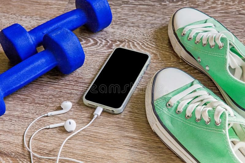 Fitness gym equipment. Sneakers, dumbbells with phone. Workout footwear. Sport trainers and music headphones royalty free stock photography