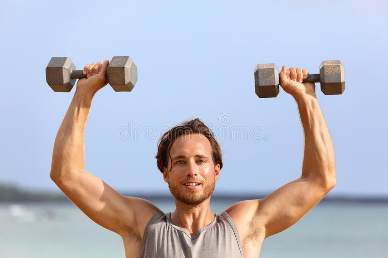Fitness gym man lifting dumbbell weights. Male athlete with muscular arms with dumbbells overhead doing shoulder press training. Biceps. Athlete holding two stock images