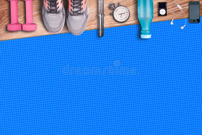 Fitness gym mat and light pink dumbbells. Fit equipment shoes and music player. royalty free stock images