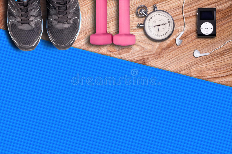 Fitness gym mat and light pink dumbbells. royalty free stock photography