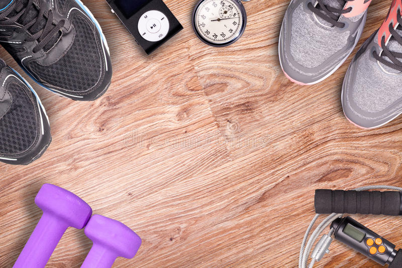 Fitness gym and running equipment. Dumbbells and running shoes, analog stopwatch and music player. Time for fitness and run. royalty free stock photography