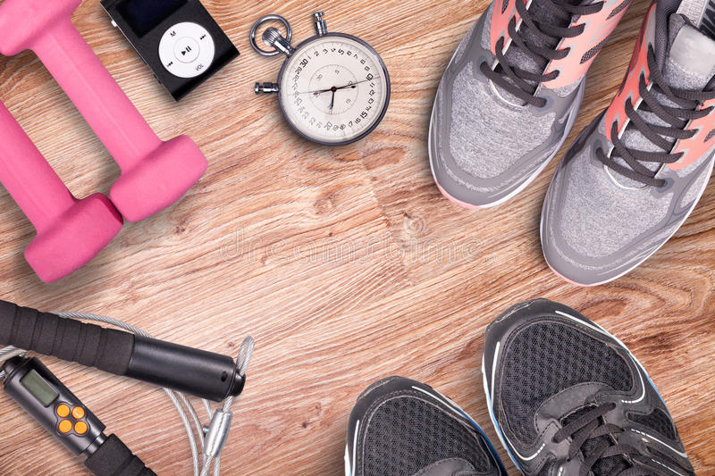 Fitness gym and running equipment. Dumbbells and running shoes, analog stopwatch and music player. Time for fitness and run. stock photos