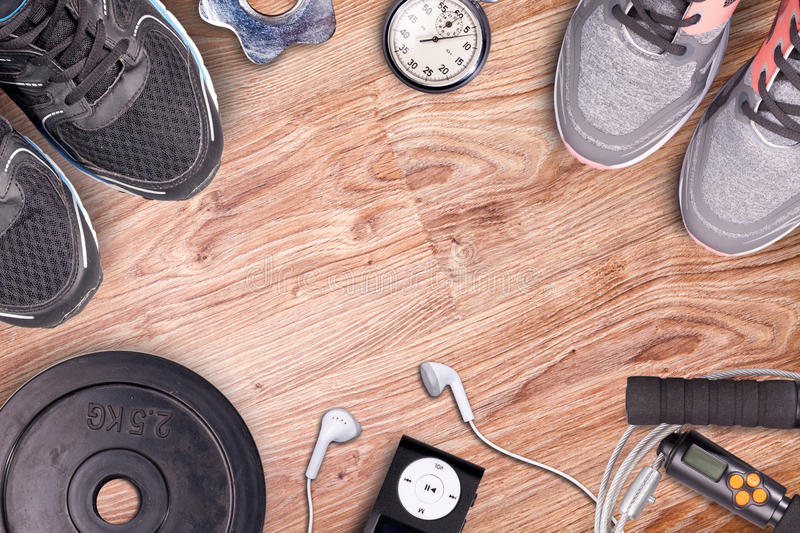 Fitness gym and running equipment. Dumbbells and running shoes, analog stopwatch and music player. stock photography