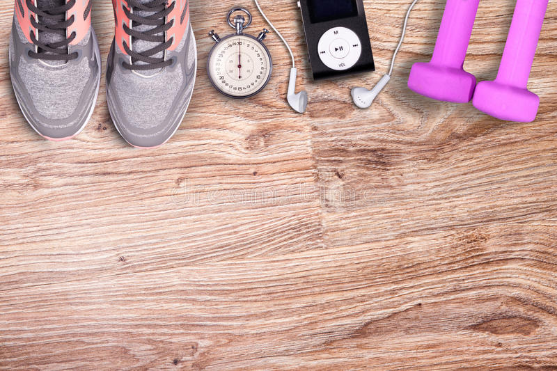 Fitness gym and running equipment. Dumbbells and running shoes, analog stopwatch and music player. stock photos
