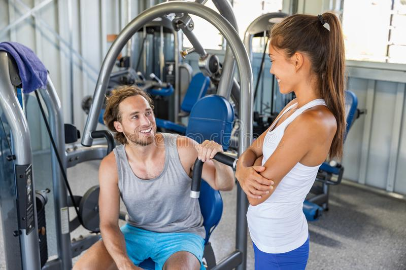 Fitness gym trainer talking to man training on workout equipment machine indoors. Couple happy working out stock photo
