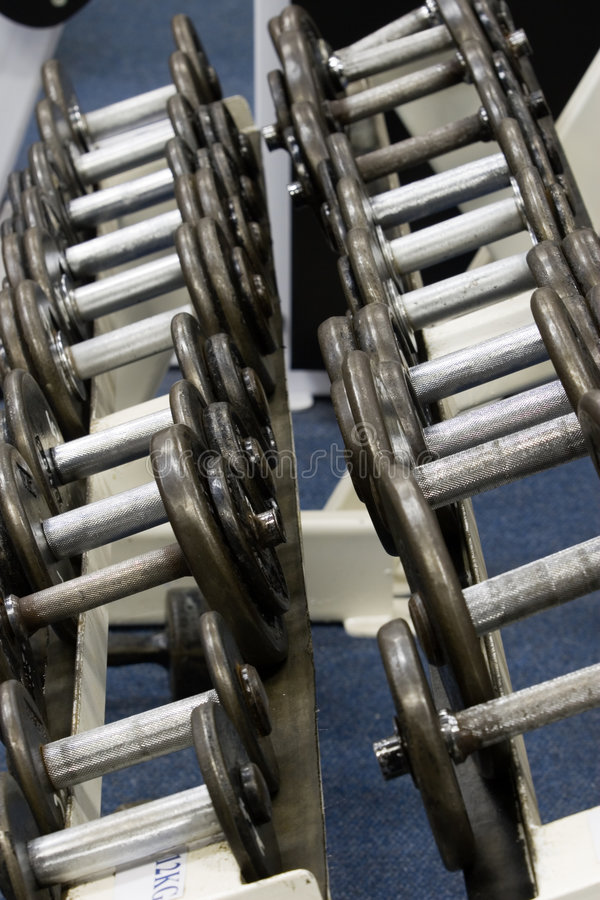 Fitness gym weights. Stack with gym weights on a blue background carpet. The photo is taken indoors under florescent light with no flash. The whole series of royalty free stock photo