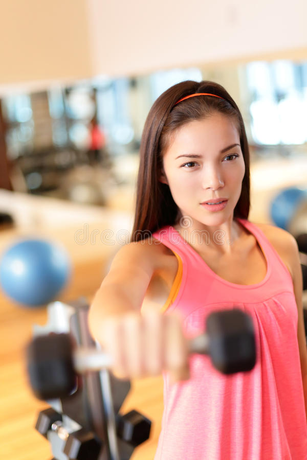 Fitness gym woman strength training lifting weights. Fitness gym woman strength training lifting dumbbell weights in shoulder exercise. Female fitness girl stock photo