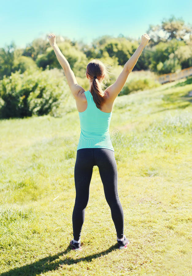 Fitness happy runner woman enjoying after training in park, runner winner, raises hands up, sport and healthy lifestyle royalty free stock photo