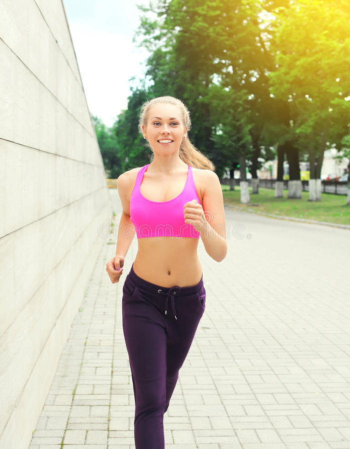 Fitness happy smiling woman running in city park, female runner workout, sport and healthy lifestyle stock image