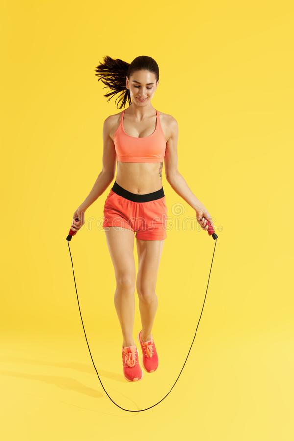 Fitness. Happy woman doing jumping exercises with skipping rope. On colorful yellow background. Full length shot of smiling girl model with fit body doing stock photography