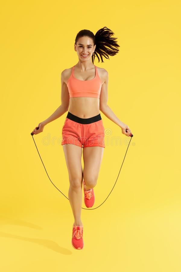 Fitness. Happy woman doing jumping exercises with skipping rope. On colorful yellow background. Full length shot of smiling girl model with fit body doing royalty free stock image