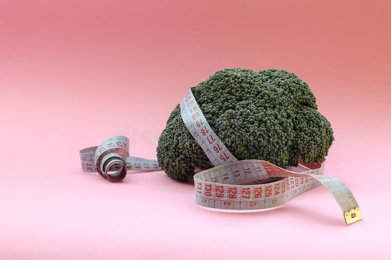 Fitness and health. Broccoli cabbage and measuring tape. Diet healthy food. Proper nutrition concept royalty free stock image