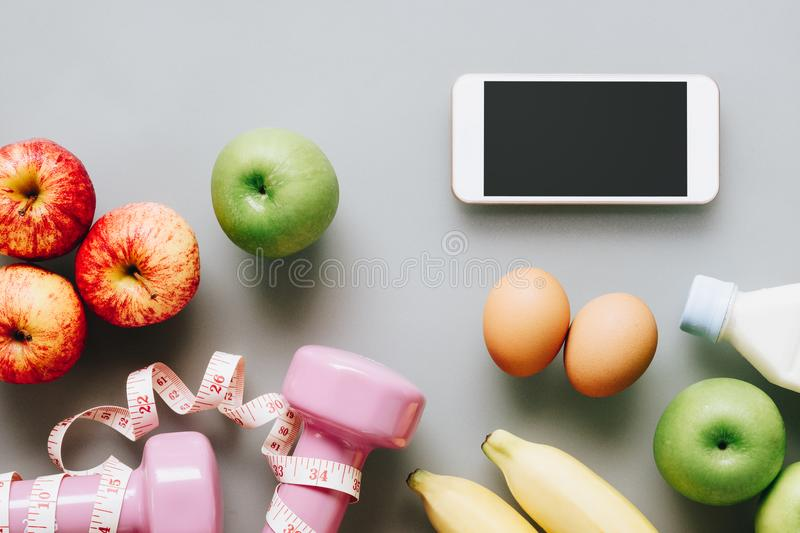 Fitness and healthy active lifestyle background concept. Dumbbell, milk bottle, apples, eggs, bananas and smart phone, tape meas. Ures on clean background. Top stock photos