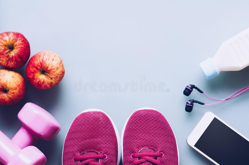 Fitness and healthy active lifestyle background concept. Dumbbell, sneakers, milk bottle, apples, ear phones and smart phone on stock image
