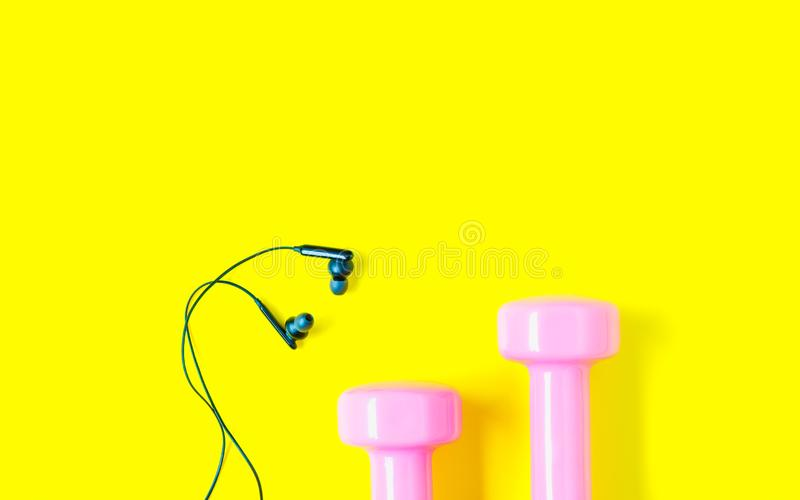 Fitness and healthy active lifestyle background concept, Equipment for gym and home pink dumbbell with black earphone on yellow royalty free stock image