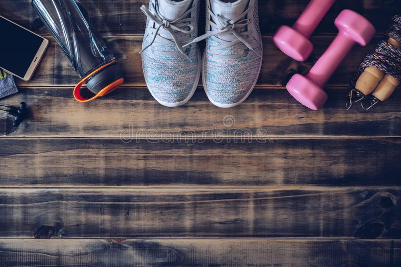 Fitness and healthy active lifestyle background concept.  Training sneakers, dumbbells, jump rope, water bottle, smart phone and stock image