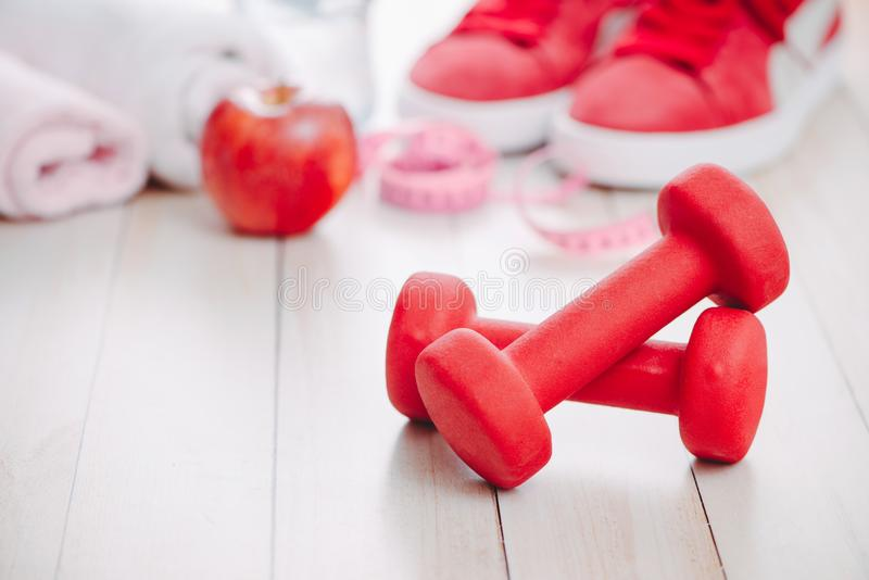 Fitness, healthy and active lifestyles Concept, dumbbells, sport. Shoes, bottle of waters and apple on wood background royalty free stock photos
