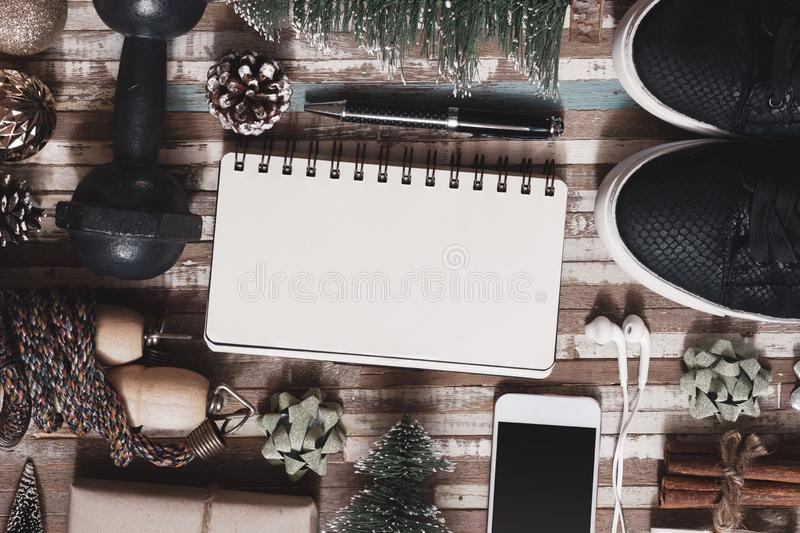 Fitness and Healthy Christmas sport composition. Overhead shot of sport shoes, dumbbells, skipping rope and Christmas ornaments. And blank space notebook for stock image