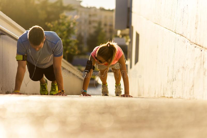 Fitness and healthy couple training while doing push-ups. Couple in sportswear doing push-ups on the ground on urban place royalty free stock photo