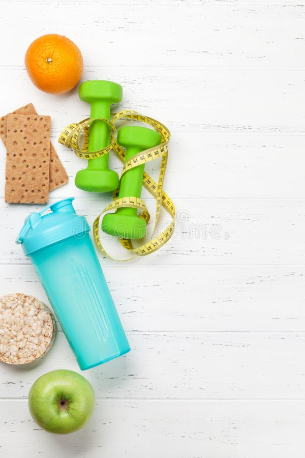 Fitness and healthy food concept. Dumbbells, fruits and drink bottle on wooden table. Top view with copy space for your text stock images