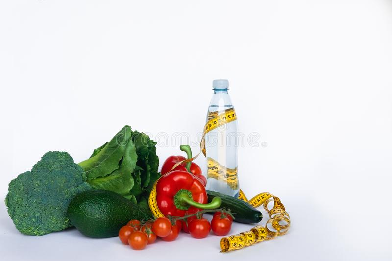 Fitness and healthy food diet concept. Vegetables and water on white background. Copy space.  royalty free stock photography