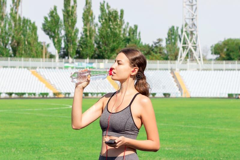 Fitness het drinkwater van de agentvrouw van een sportfles energiedrank op de opleiding bij stadion Sporten en gezond concept stock foto's