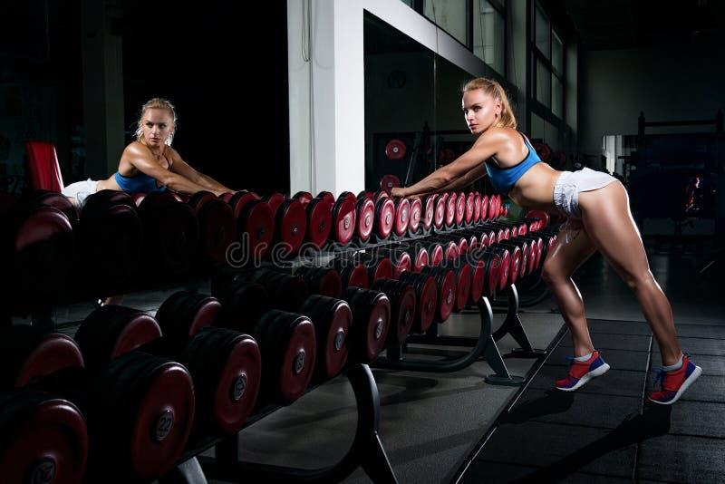 Fitness is het jonge zwetende meisje met een sportenlichaam in de gymnastiek sexua stock fotografie