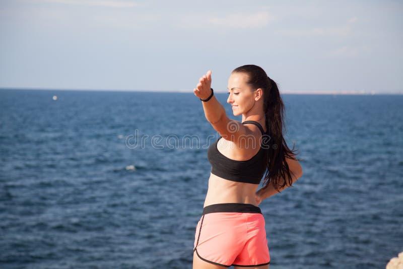 Fitness het Sportenmeisje leidt de spieren op het strand op stock fotografie