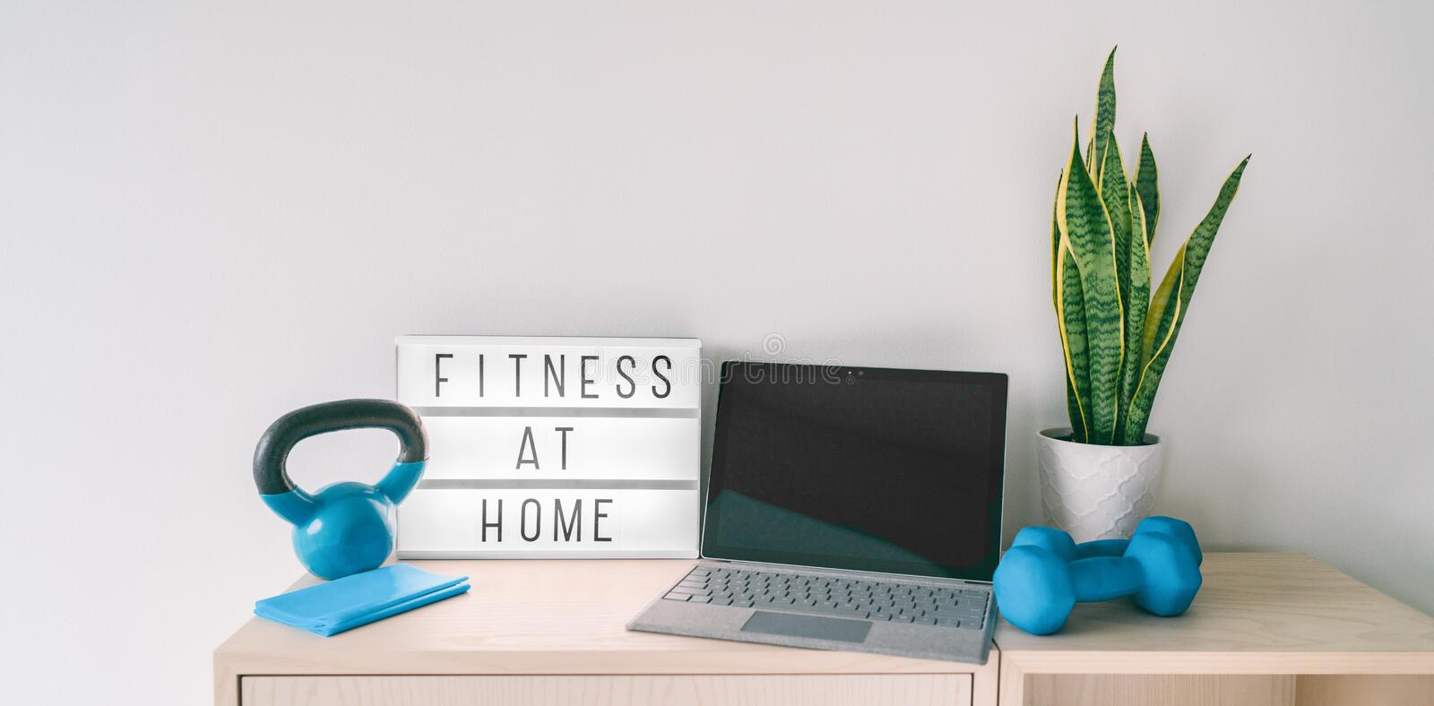 Fitness at home online exercise class on computer laptop with training weights and resistance band. Coronavirus COVID-19 stock image