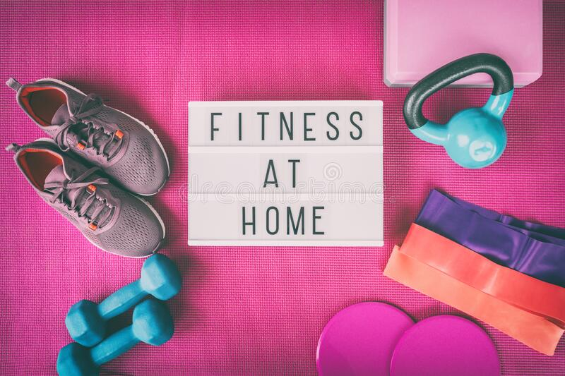 Fitness at home sign with pink yoga mat, running shoes, kettlebell weight and dumbells resistance bands and sliders for stock image