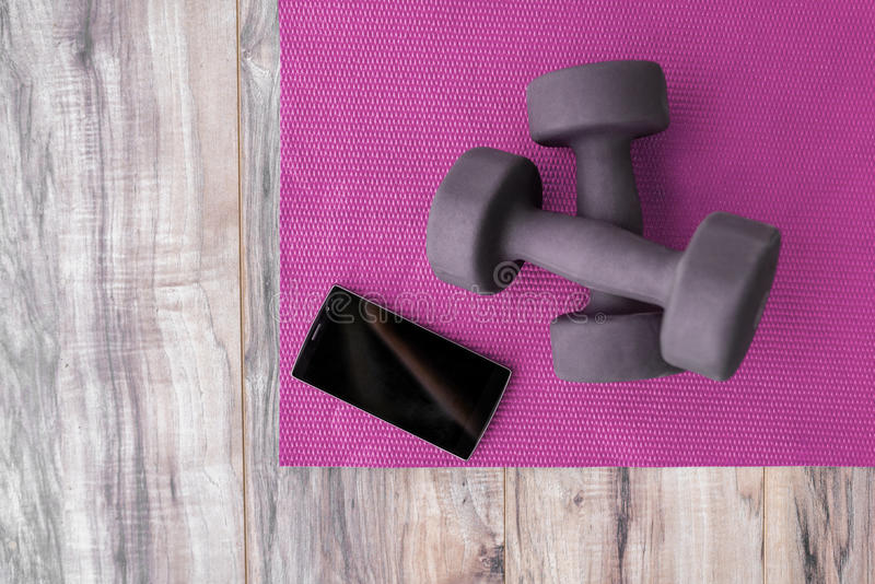 Fitness at home-weights yoga mat mobile phone app royalty free stock photography