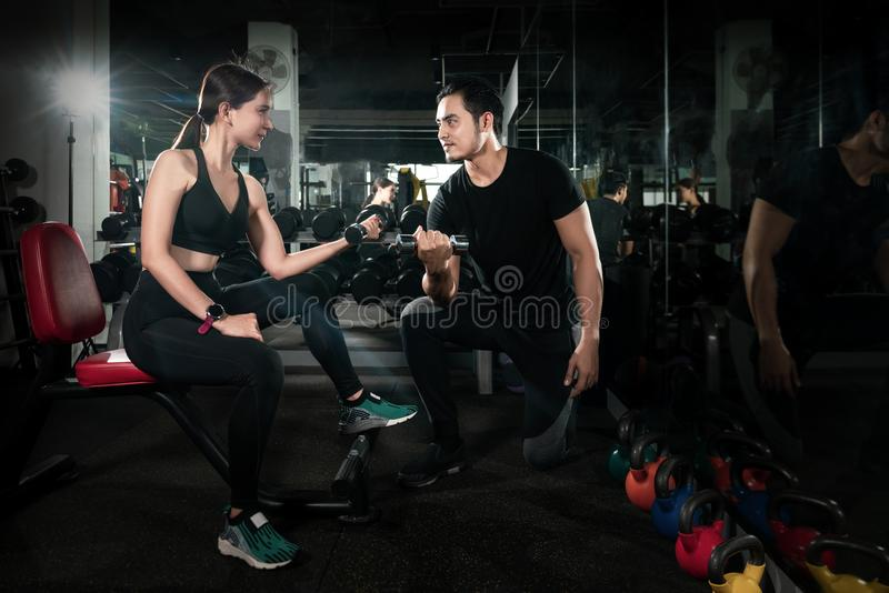 Fitness instructor exercising with his client at the gym, Personal trainer helping woman working with heavy dumbbells stock images