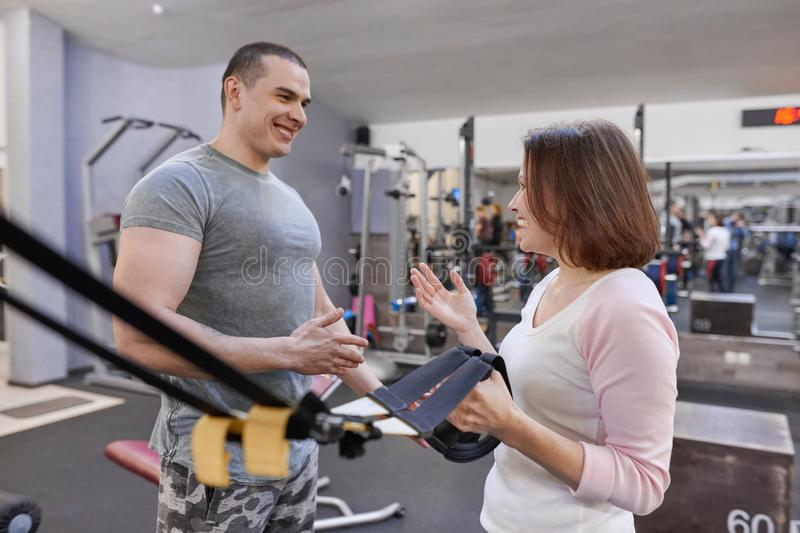Fitness instructor and mature woman at gym. Male sports instructor and middle-aged woman talking and laughing in health club stock photo