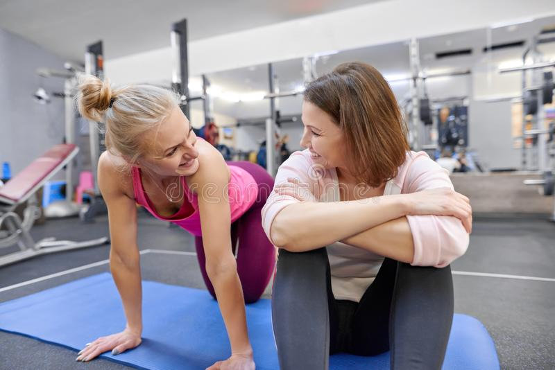 Fitness instructor and mature woman at gym. Female sports instructor and middle-aged woman talking smiling and laughing in health stock image