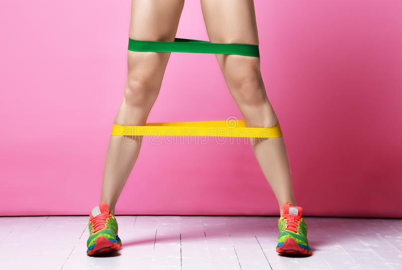 Fitness instructor woman legs exercising working out with green and yellow rubber resistance band on modern pink royalty free stock image