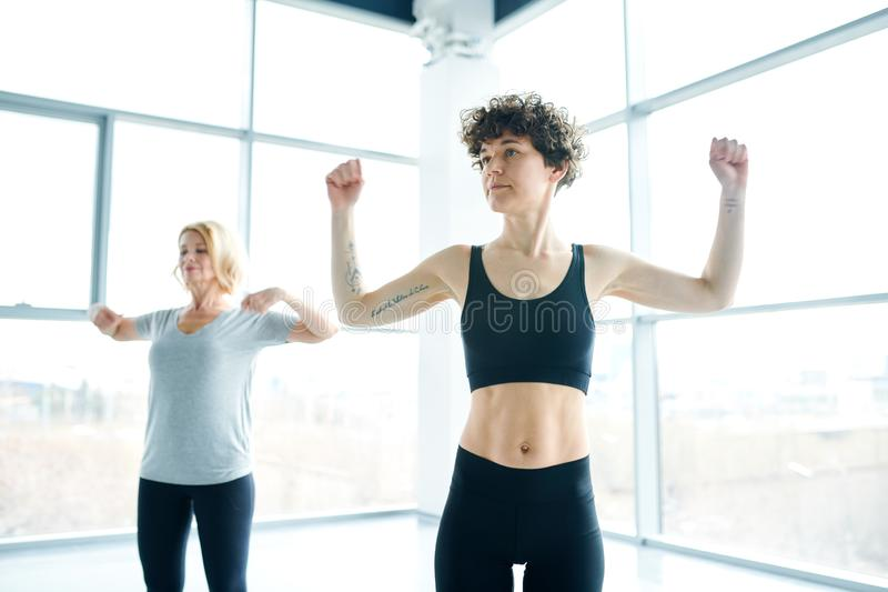 Fitness instructor. Young fitness trainer in black tracksuit showing exercises for arms to her group with mature female on background repeating after her royalty free stock image