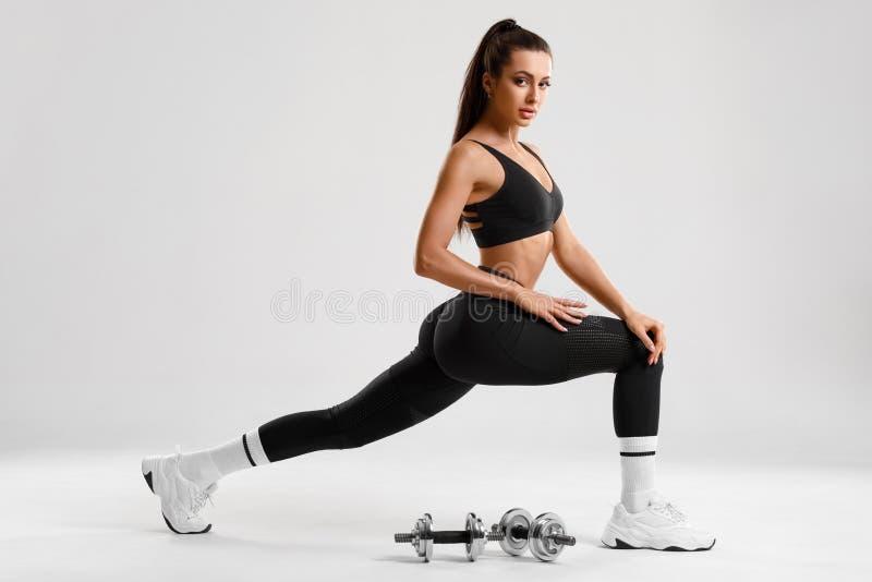 Fitness kobieta ćwicząca ćwiczenia w płucach na treningu mięśni kończyn Aktywna dziewczynka, wykonująca ćwiczenia na jednym kroku zdjęcie royalty free