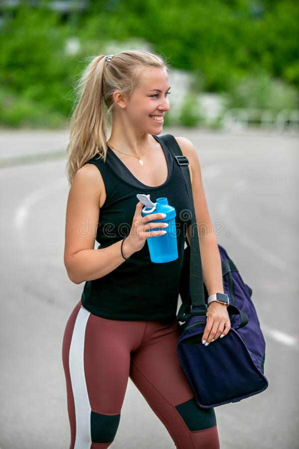 Fitness lifestyle. Athletic young woman drinks water from a bottle after a workout. Training at the stadium. Healthy lifestyle royalty free stock photos