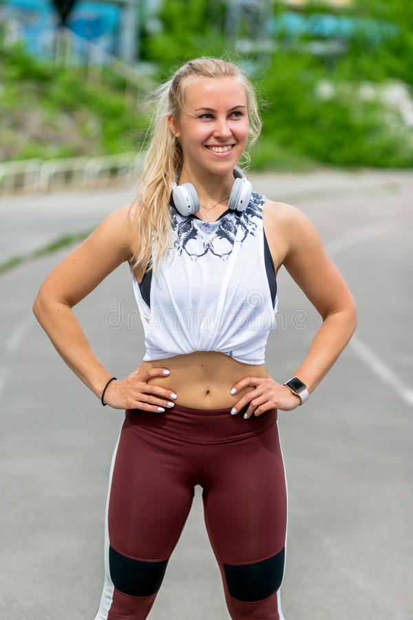 Fitness lifestyle. Athletic young woman with headphones poses during a training. Workout at the stadium. Healthy life concept. royalty free stock image