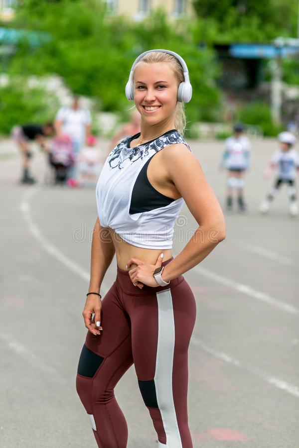 Fitness lifestyle. Athletic young woman poses in headphones. Workout at the stadium. Healthy life concept. Vertical photo royalty free stock photo
