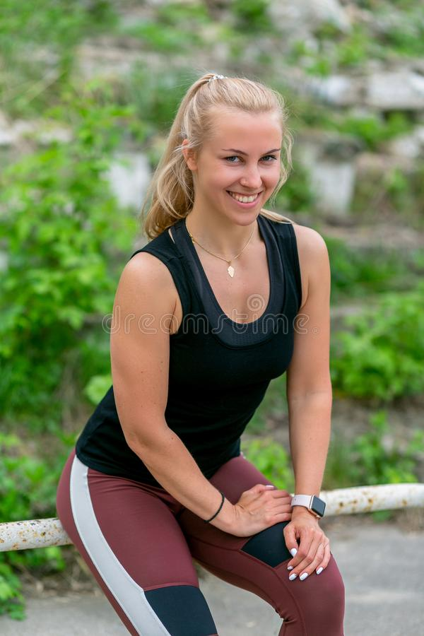 Fitness lifestyle. Athletic young woman sits on the railing after a workout. Workout at the stadium. Healthy life concept. royalty free stock image