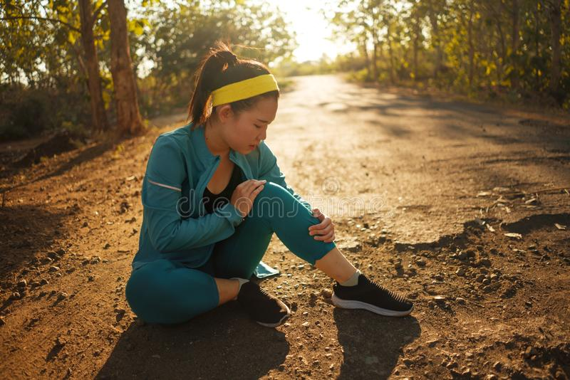 Fitness lifestyle portrait of young attractive Asian Chinese runner woman suffering sport injury during jogging workout on sunset stock photo