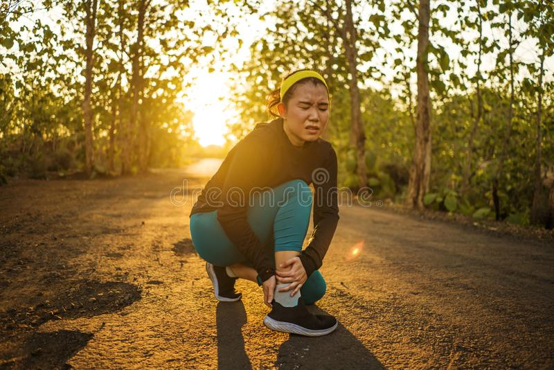 Fitness lifestyle portrait of young attractive Asian runner woman suffering sport injury during jogging workout on sunset road royalty free stock photos