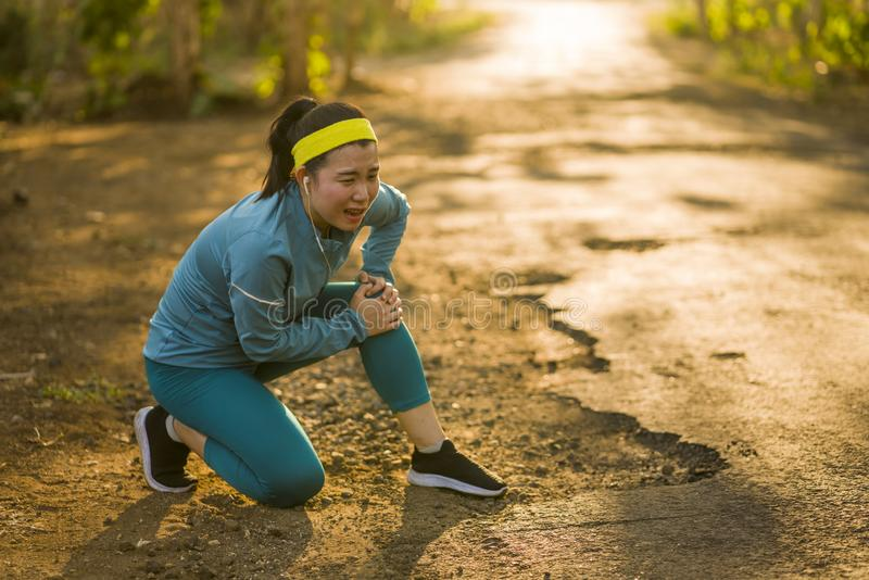 Fitness lifestyle portrait of young attractive Asian runner woman suffering sport injury during jogging workout on sunset road stock photo