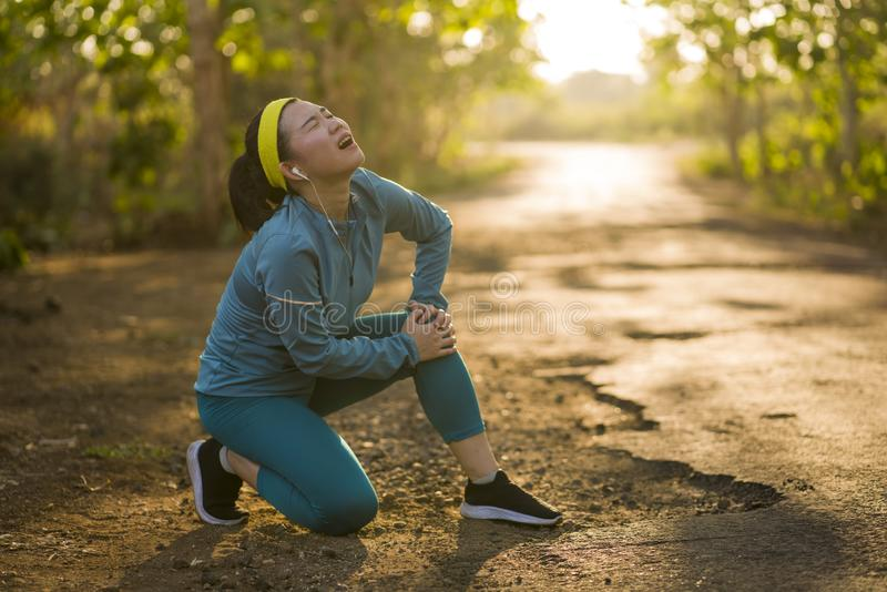 Fitness lifestyle portrait of young attractive Asian runner woman suffering sport injury during jogging workout on sunset road royalty free stock photography